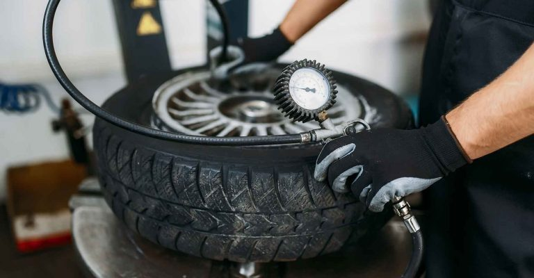 Mechanic inflates the wheel, tire repairing service. Man repairs car tyre in garage, professional automobile inspection in workshop
