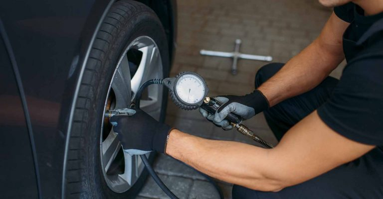Auto mechanic checks the tire pressure in repairing service. Man repairs car tyre in garage, professional automobile inspection in workshop