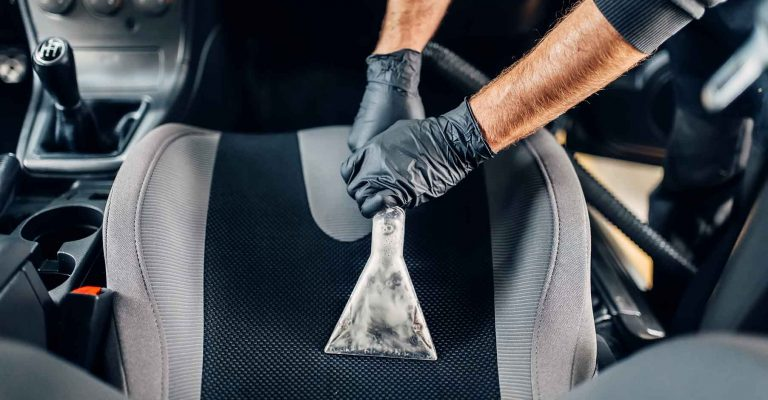 Professional dry cleaning of car interior with vacuum cleaner. Carwash service, male worker in gloves removes dust
