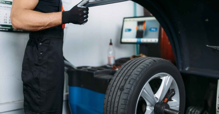 Mechanic fixing broken wheel on the balancing machine, tire service. Man repairs car tyre in garage, automobile on lift jack, inspection in workshop