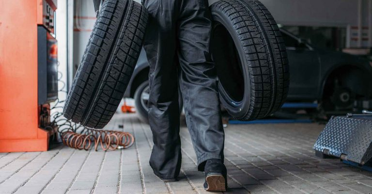 Auto mechanic holds two new tires, repairing service. Worker repairs car tyre in garage, professional automobile inspection in workshop